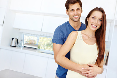 Buy stock photo Cute young couple standing together in their kitchen at home