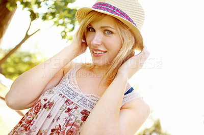 Buy stock photo Portrait of a smiling blonde with a hat on in the park