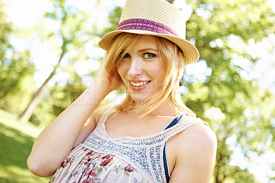 Buy stock photo Portrait of cute smiling blonde posing with a hat in the park