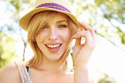 Buy stock photo Portrait of a pretty smiling blonde holding on to her hat in the park