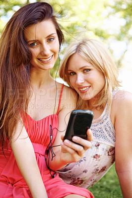 Buy stock photo Portraits of girl friends listening to music on their phone and sitting in the park bonding