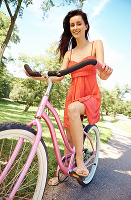 Buy stock photo Portrait of pretty brunette on her bicycle in the park