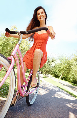 Buy stock photo A pretty brunette on her bicycle in the park with copyspace