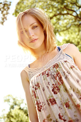 Buy stock photo A low angle view of a beautiful young woman in a park with the sun shining behind her