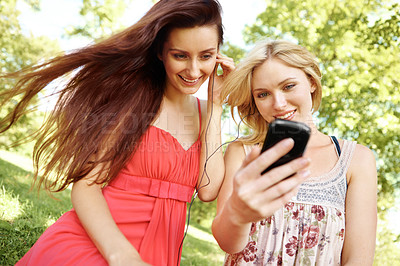 Buy stock photo Two beautiful friends watching clips on a smartphone in the park