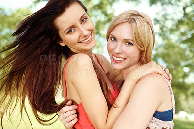 Buy stock photo Two beautiful friends embracing in a park