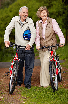 Buy stock photo Full length of a happy mature couple standing with bicycle in countryside