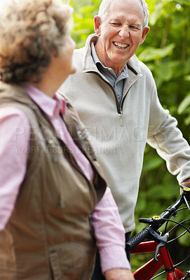 Buy stock photo Portrait of a happy mature man with senior woman riding bicycle in countryside