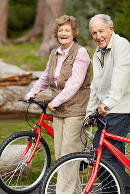 Buy stock photo Portrait of a happy senior couple standing with their bicycles in countryside - portrait