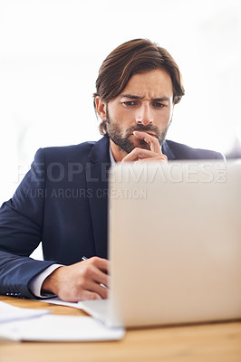 Buy stock photo A handsome businessman deep in thought while working on his laptop