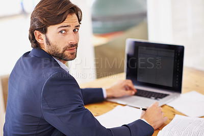 Buy stock photo Shot of a confident young businessman working on his laptop and looking at the camera
