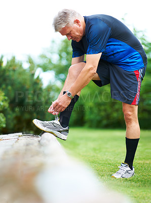 Buy stock photo Middle-aged jogger resting his foot on a chair while tying his shoelace