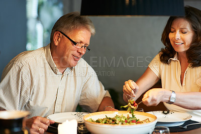 Buy stock photo Cropped shot of a senior couple sharing a romantic meal at home