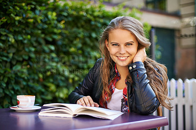 Buy stock photo Portrait of an attractive teen reading a book at a bistro