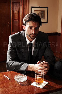 Buy stock photo Portrait of a well-dressed young man sitting at a bar with a drink