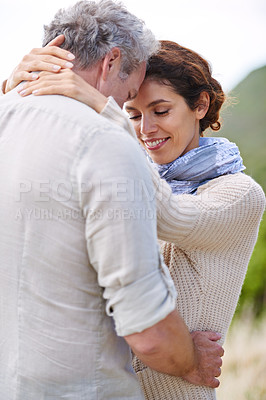 Buy stock photo Sideways shot of a mature loving couple standing face to face and hugging