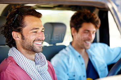 Buy stock photo Two young male friends sharing a joke while driving