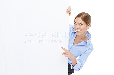 Buy stock photo Studio shot of a beautiful young businesswoman pointing towards your copyspace on a blank white wall