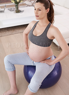 Buy stock photo Shot of a young pregnant woman exercising at home