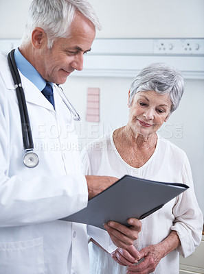 Buy stock photo Shot of a doctor discussing a medical chart with a senior patient
