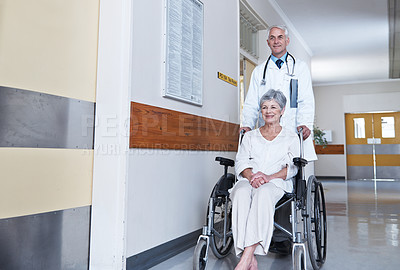 Buy stock photo Shot of a male doctor wheeling a senior patient down a hospital hallway