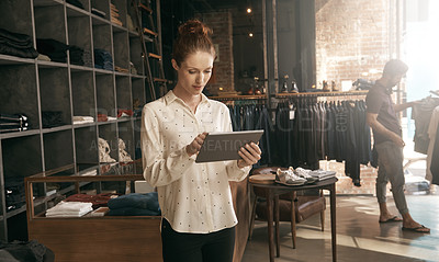 Buy stock photo Shot of a young shop owner working on a digital tablet with a customer in the background