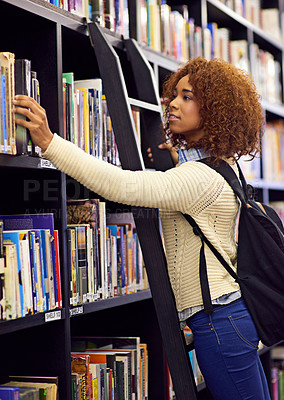 Buy stock photo Shot of a young woman reaching for a book from a bookshelf in a university library