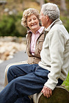 Happy mature couple sitting on log in countryside