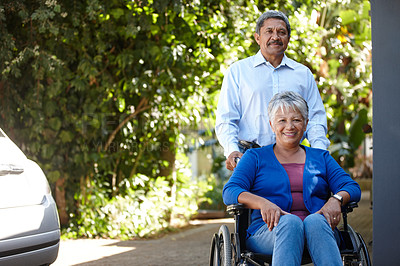 Buy stock photo Portrait of a senior man pushing his wife in a wheelchair outdoors