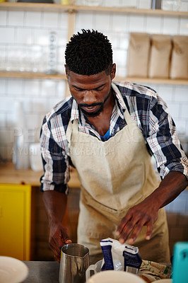 Buy stock photo Cropped shot of a male barista making a cup of coffee in a cafe