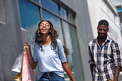 Buy stock photo A beautiful woman posing with her shopping bags with a man standing in the background