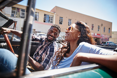 Buy stock photo A happy young couple driving in a convertible on a bright summer's day
