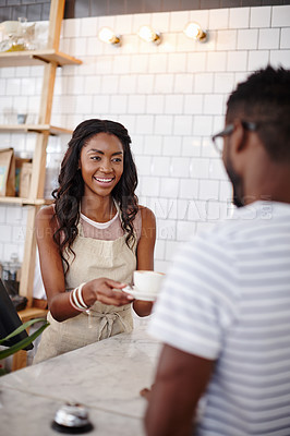 Buy stock photo A young female barista serving a customer a cup of coffee