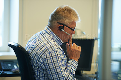 Buy stock photo Shot of a senior businessman wearing a headset looking thoughtful while sitting at his computer