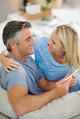 Buy stock photo Shot of a laughing couple sitting at home using a digital tablet