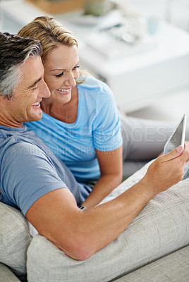 Buy stock photo Shot of a smiling couple sitting at home using a digital tablet