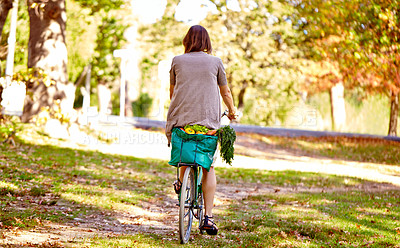 Buy stock photo Rearview shot of a young woman riding her bicycle home from the grocery store