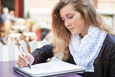 Buy stock photo A young woman drawing in her notepad