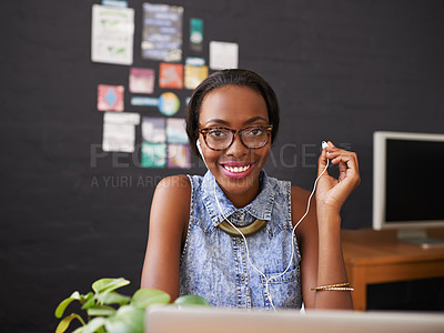 Buy stock photo Shot of a young designer listening to music through her earphones