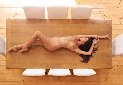 Buy stock photo Shot of a beautiful naked woman lying on a dining room table