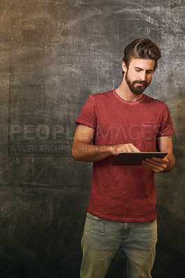Buy stock photo Cropped shot of a handsome young man using a tablet against a grunge background