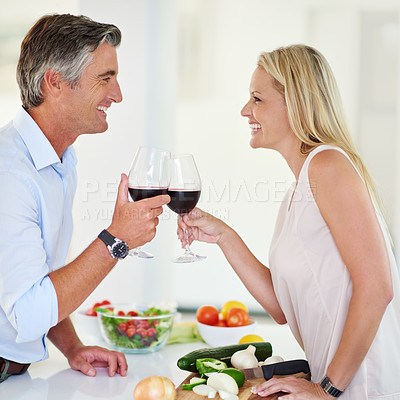 Buy stock photo Shot of an affectionate couple toasting with red wine while making dinner