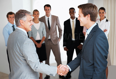 Buy stock photo Two successful businessman shaking hands in front of corporate team at office