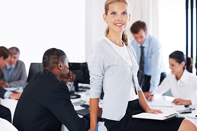 Buy stock photo Portrait of a smiling young businesswoman sitting with a file on the desk and her colleagues working behind at office