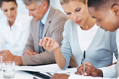 Buy stock photo Successful business people doing some paperwork during a meeting