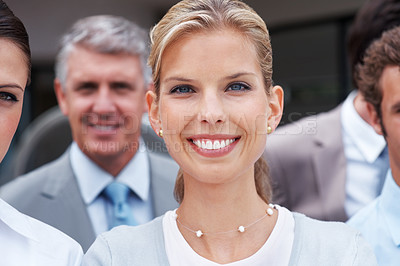 Buy stock photo Portrait of a smiling young businesswoman standing together with her colleagues