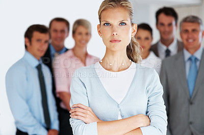 Buy stock photo Portrait of a successful young businesswoman standing with his hands folded with her colleagues in background