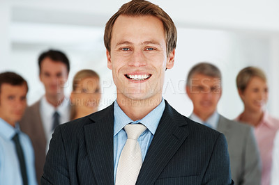 Buy stock photo Portrait of handsome executive smiling with colleagues in background