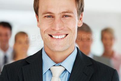 Buy stock photo Closeup portrait of a happy young businessman smiling and his team in background