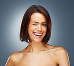 Naked woman giving you winking smile against colored background